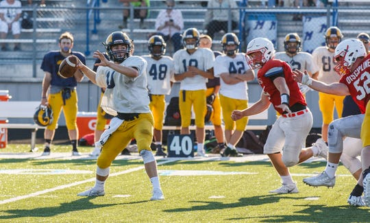 Marquette quarterback Michael McDevitt drops back to pass Friday during a scrimmage against Homestead at Mukwonago High School.