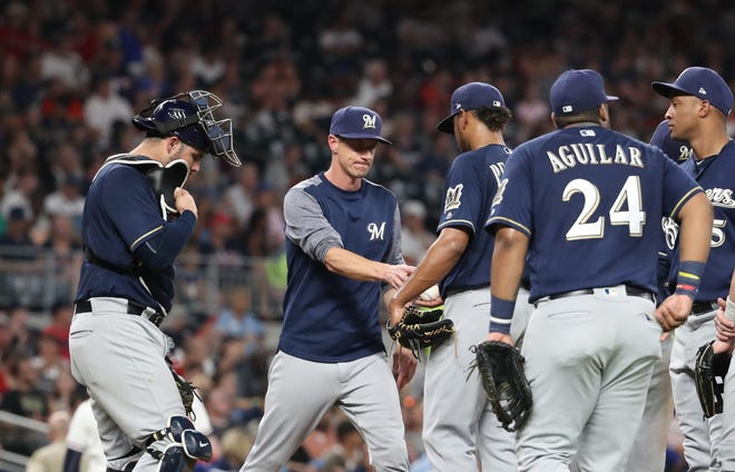 Brewers manager Craig Counsell  removes starting pitcher Freddy Peralta in the fourth inning Friday night in Atlanta.