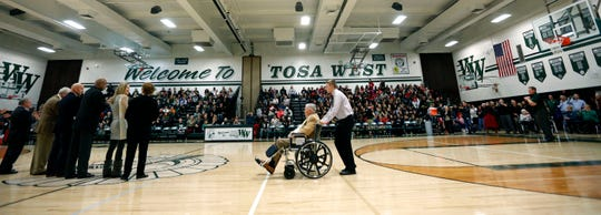 Bob White Sr. is wheeled onto center court during a Wauwatosa West High School Athletic Hall of Fame Induction ceremony on Jan. 17, 2015, in Wauwatosa. White Sr. served for 40 years as a swim coach, first for 10 years at what is now Wauwatosa East High School and later at Wauwatosa West High School.