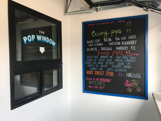Pops are sold from a window. Customers can pause at a counter beside an open window to eat their pops.