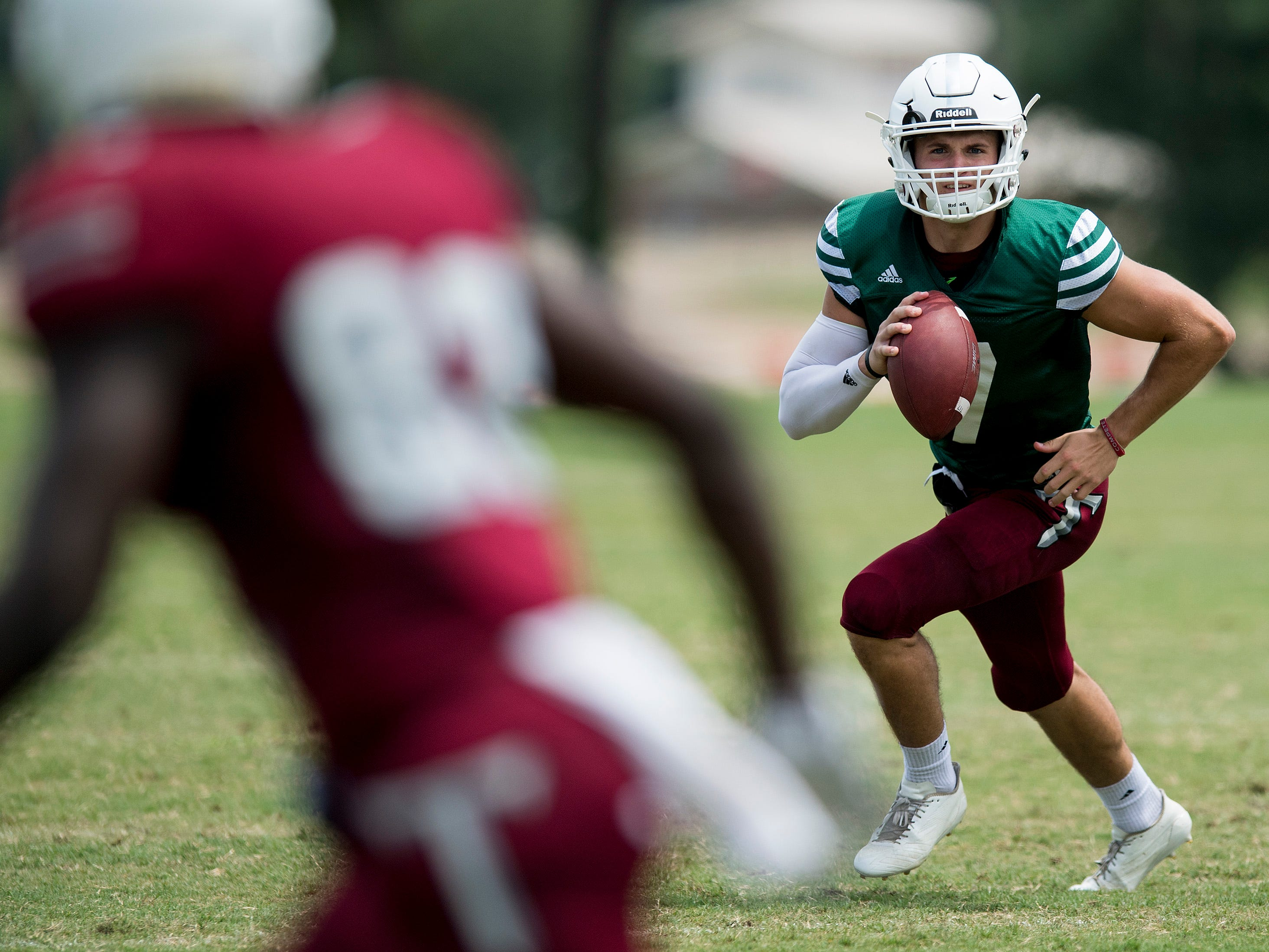 Troy University quarterback Kaleb Barker rolls out during the scrimmage in Troy, Ala. on Saturday August 11, 2018.