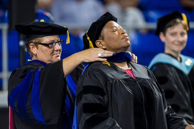 MTSU doctoral candidate Rita Whitaker, right, receives her academic hood from MTSU associate professor Joey Gray during Saturday's summer commencement ceremony in Murphy Center.