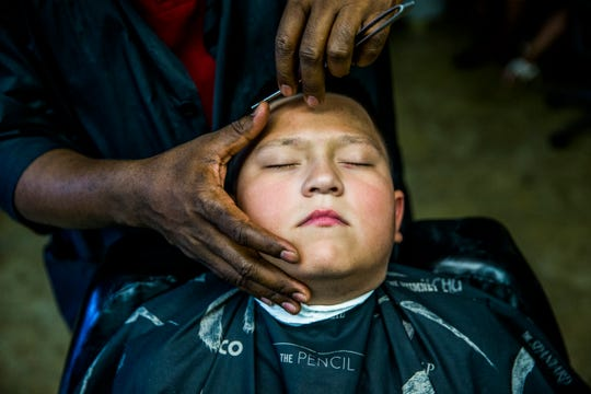 Rising fourth grader Cristopher Cardena gets a haircut at Excelsior barbershop in River Park on Saturday, Aug. 11, 2018. The shop offered free haircuts and backpacks for kids to get ready to go back to school.