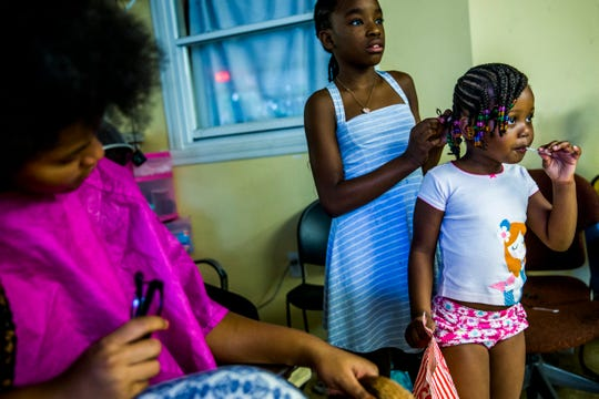 Rising fourth grader Christelle Preeals helps Sabrina Reveau, 4, with her hair at Excelsior barbershop in River Park on Saturday, Aug. 11, 2018. The shop offered free haircuts and backpacks for kids to get ready to go back to school.