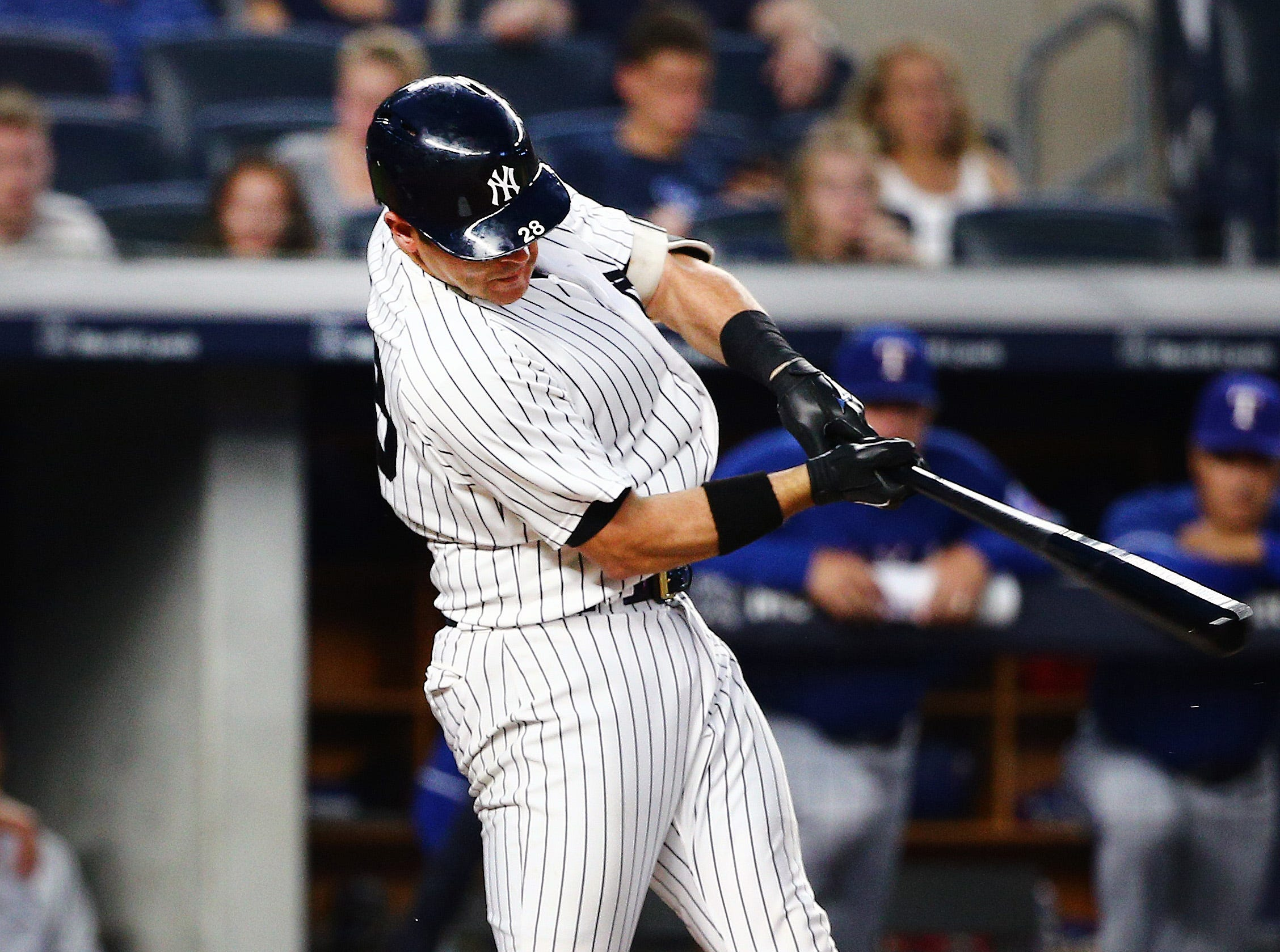 Yankees catcher Austin Romine (28) singles against the Texas Rangers during the third inning at Yankee Stadium.