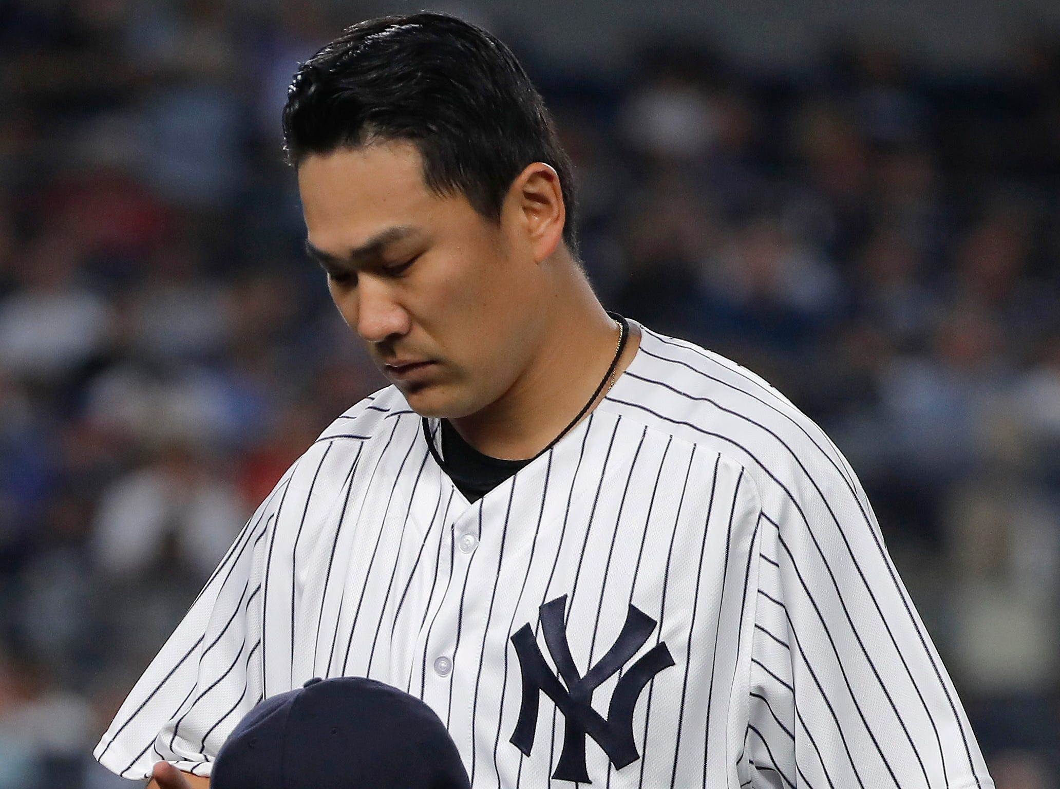 New York Yankees starting pitcher Masahiro Tanaka walks off the field at the end of the top of the fourth inning of a baseball game against the Texas Rangers, Friday, Aug. 10, 2018, in New York.