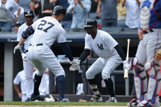 Aug 11, 2018; Bronx, NY, USA; New York Yankees designated hitter Giancarlo Stanton (27) celebrates his solo home run against the Texas Rangers with shortstop Didi Gregorius (18) during the first inning at Yankee Stadium.