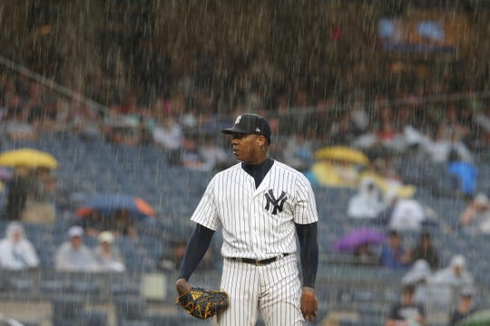 Aug 11, 2018; Bronx, NY, USA; New York Yankees relief pitcher Aroldis Chapman (54) pitches in the rain against the Texas Rangers during the ninth inning at Yankee Stadium.