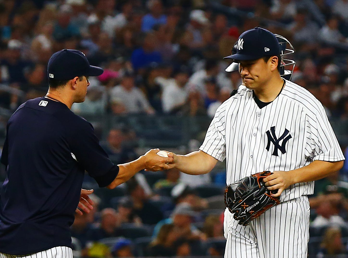 Aug 10, 2018; Bronx, NY, USA; New York Yankees starting pitcher Masahiro Tanaka (19) hands the ball to manager Aaron Boone (17) after being taken out of the game against the Texas Rangers during the sixth inning at Yankee Stadium. Mandatory Credit: Andy Marlin-USA TODAY Sports