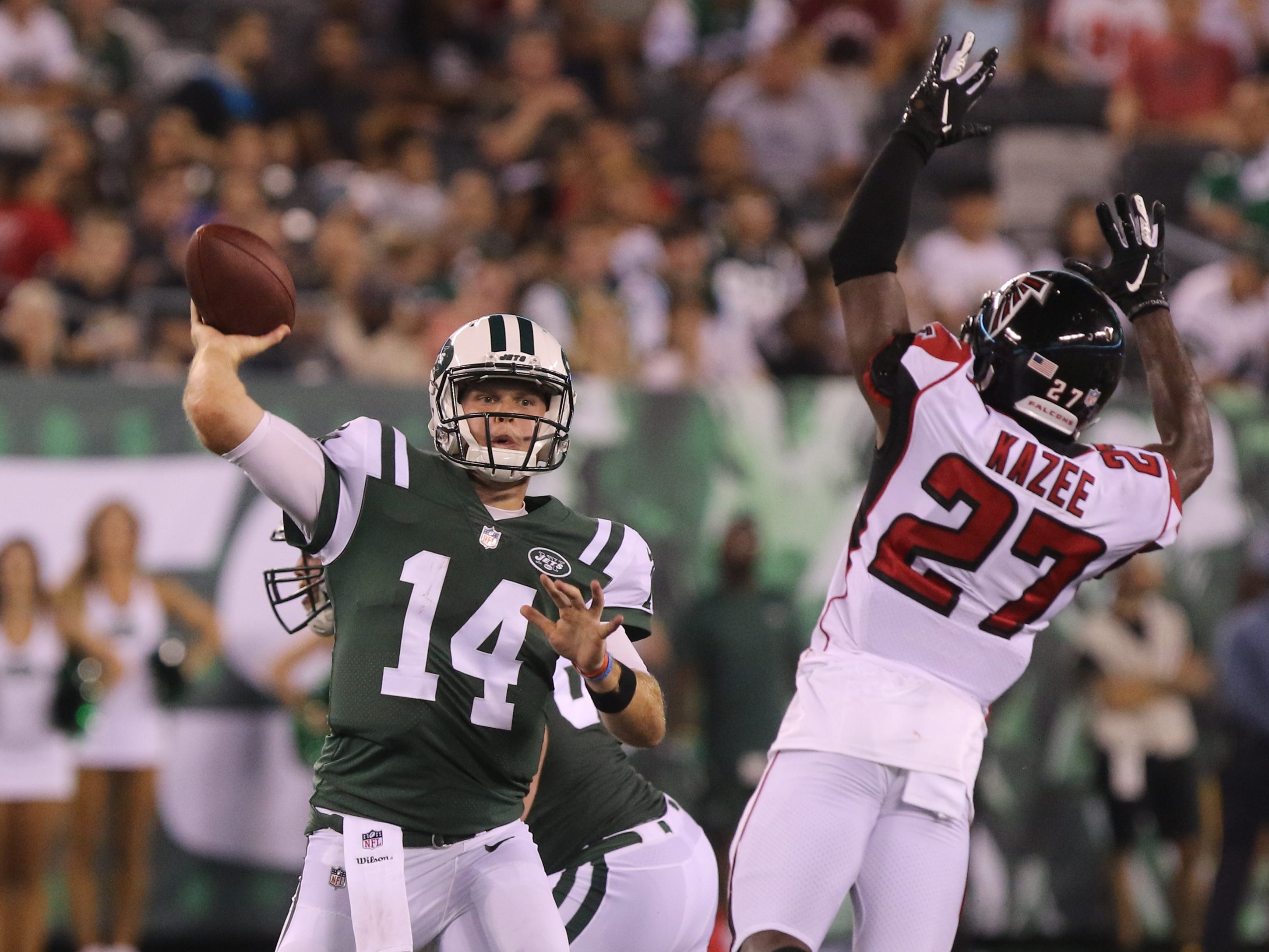 Jets quarterback Sam Darnold stands tall as he gets the ball past Damontae Kazee of the Falcons during preseason action at MetLife Stadium, East Rutherford, on Friday, Aug. 10, 2018.
