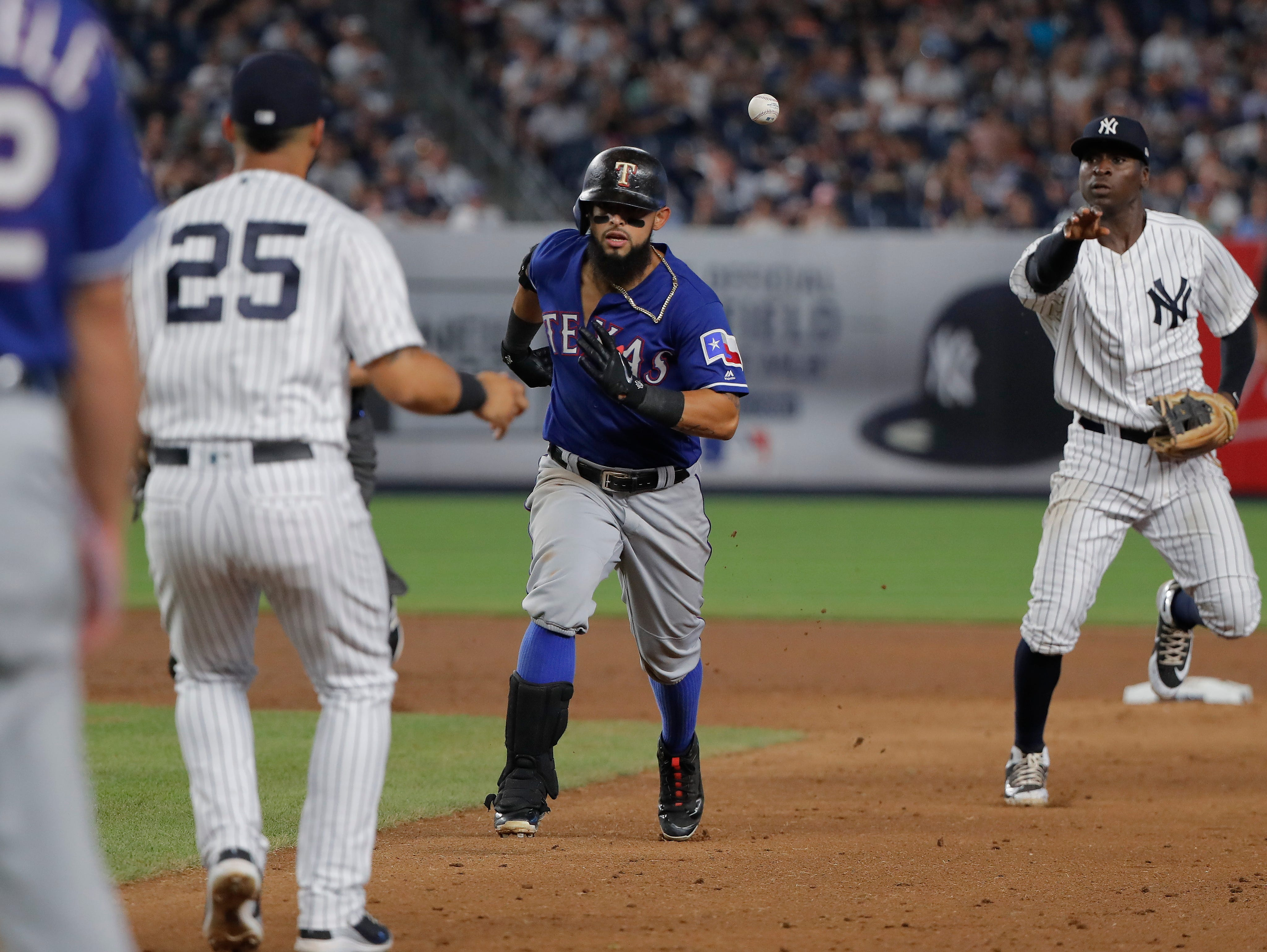 Texas Rangers' Rougned Odor, center, is caught in a rundown as New York Yankees shortstop Didi Gregorius, right, throws to second baseman Gleyber Torres (25) during the sixth inning of a baseball game, Friday, Aug. 10, 2018, in New York. Gregorius made an error on the throw and Odor advanced to second base on the play.