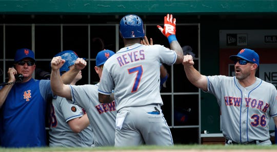 New York Mets' Jose Reyes is congratulated at the dugout by manager Mickey Callaway, right, after hitting a solo home run in the eighth inning of a baseball game against the Washington Nationals at Nationals Park, Wednesday, Aug. 1, 2018, in Washington. The Nationals won 5-3.