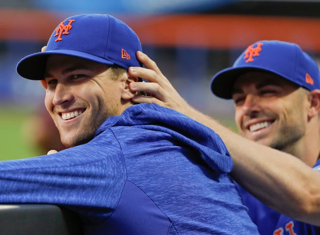 New York Mets' David Wright, right, jokes with pitcher Jacob deGrom in the dugout during the team's baseball game against the Pittsburgh Pirates, Tuesday, June 26, 2018, in New York.