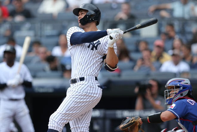 Aug 11, 2018; Bronx, NY, USA; New York Yankees designated hitter Giancarlo Stanton (27) follows through on a solo home run against the Texas Rangers at Yankee Stadium.