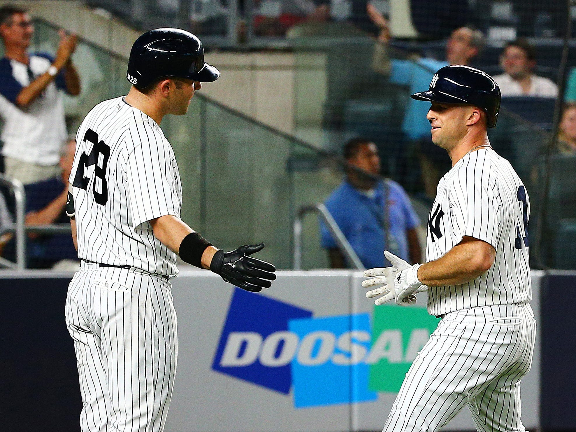 Yankees left fielder Brett Gardner (11) is congratulated by catcher Austin Romine (28) after hitting a solo home run against the Texas Rangers during the fifth inning at Yankee Stadium.