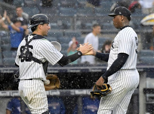 New York Yankees pitcher Aroldis Chapman, right, and catcher Kyle Higashioka celebrate after the Yankees defeated the Texas Rangers 5-3 in a baseball game Saturday, Aug. 11, 2018, at Yankee Stadium in New York.