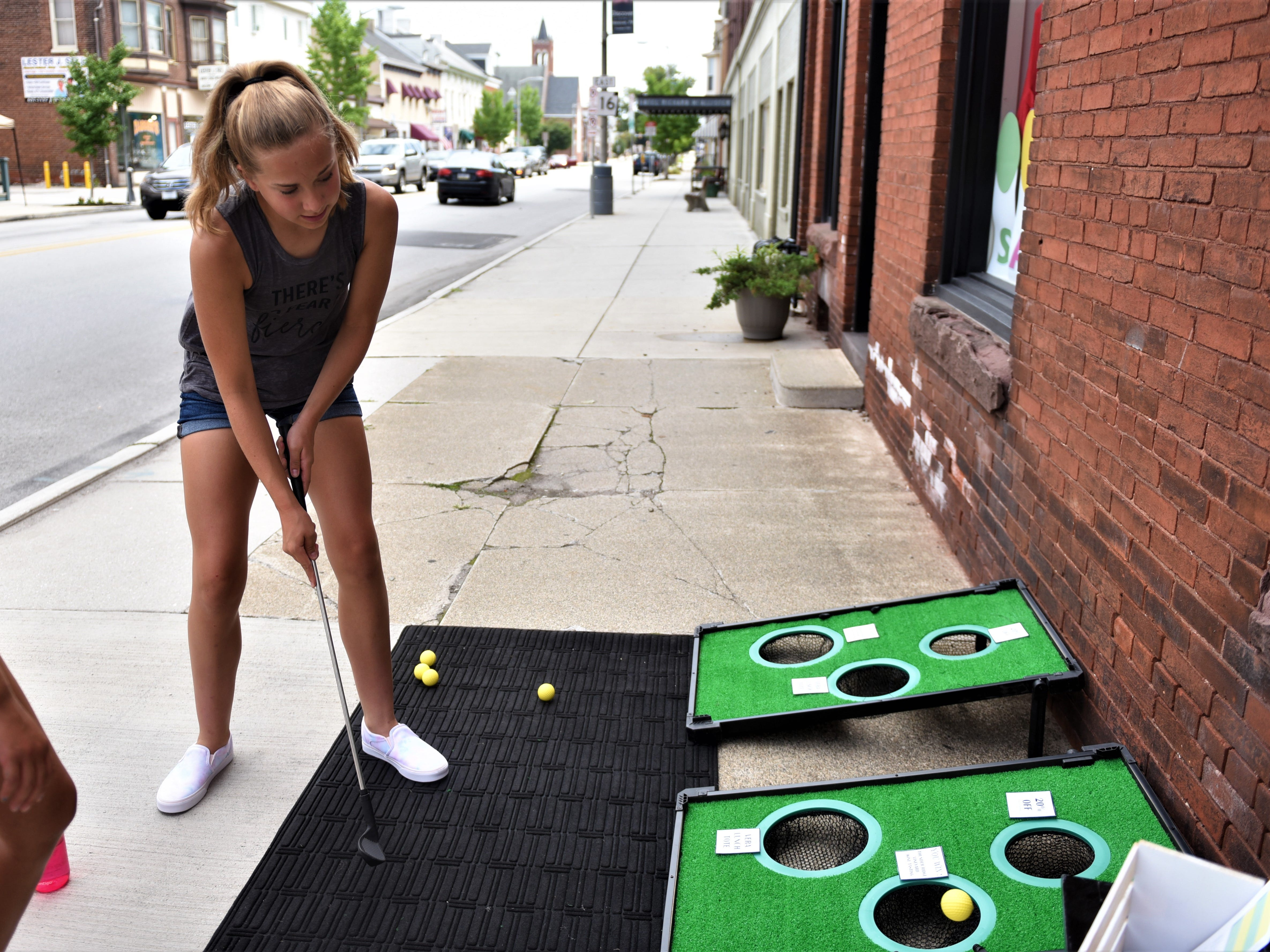 Reagan Wildasin, 13, gets a hole-in-one at the Treasures mini golf hole.