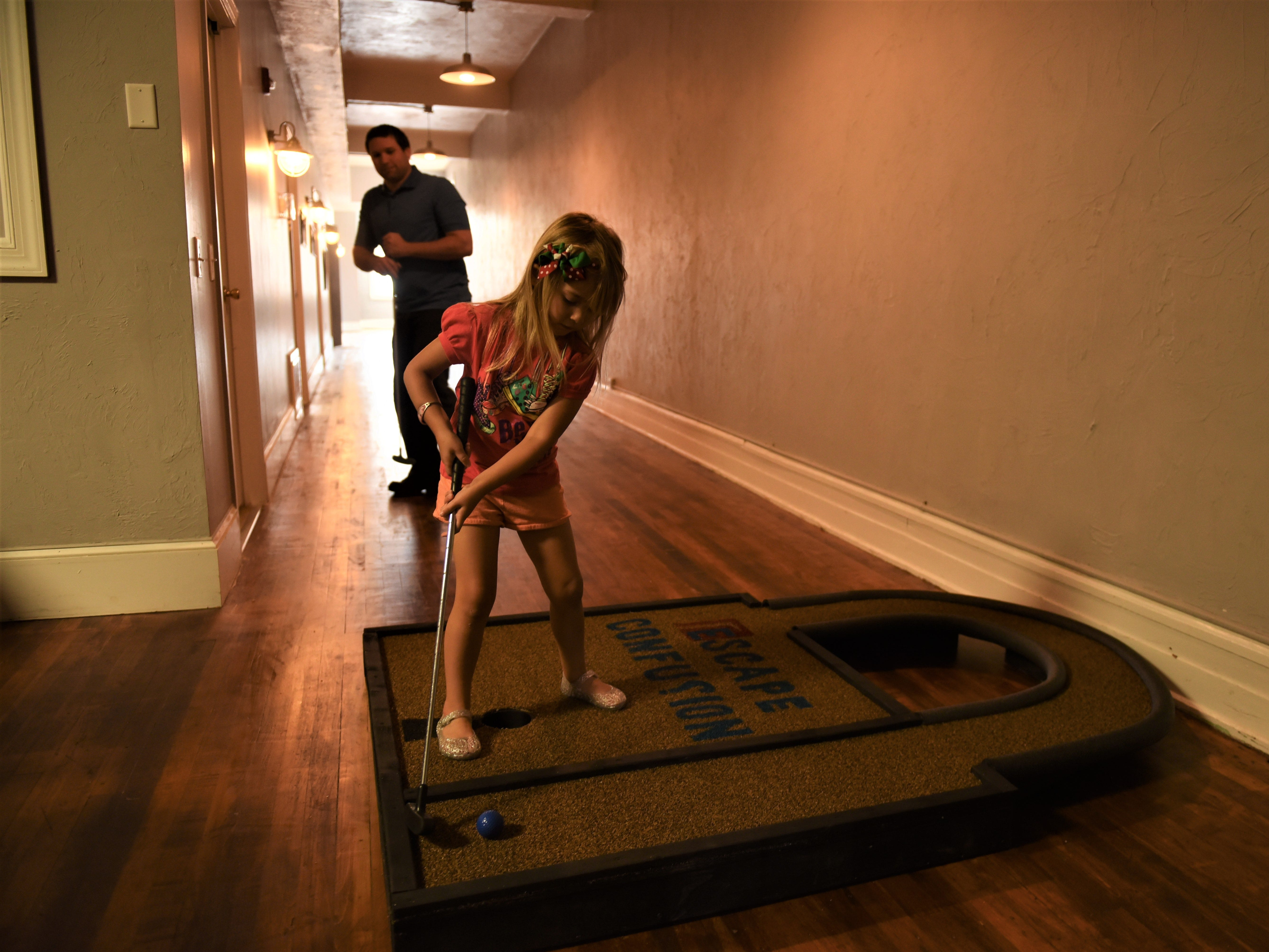 London Bouligny, 5, takes a swing at Escape Confusion for the Second Saturday mini golf event.
