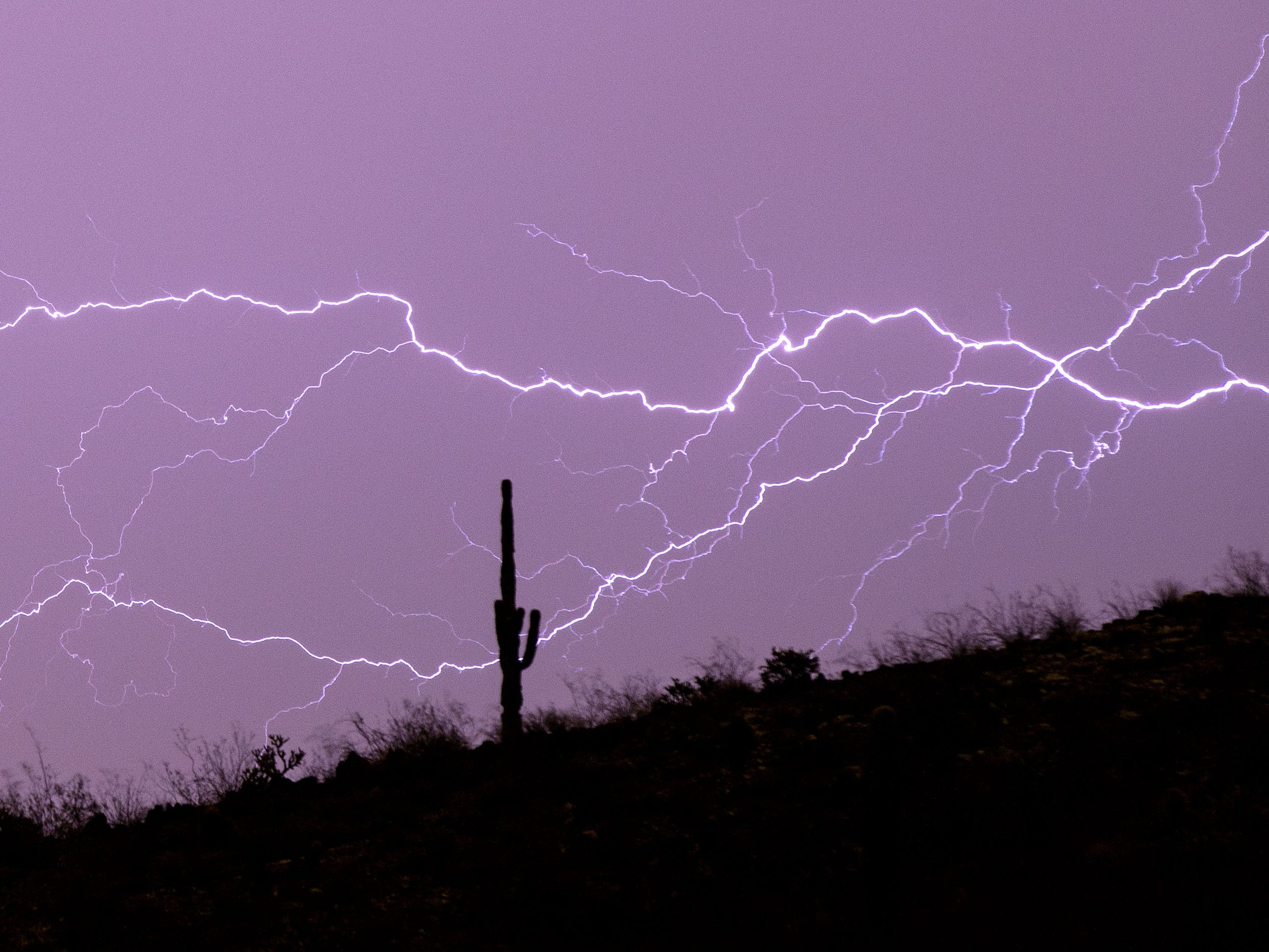 Lightning streaks across the sky over the Phoenix Mountain Preserve during a monsoon storm on Aug. 10, 2018, in Phoenix.