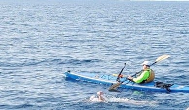 Elizabeth Fry swims next to a kayaker on her way across Lake Huron.