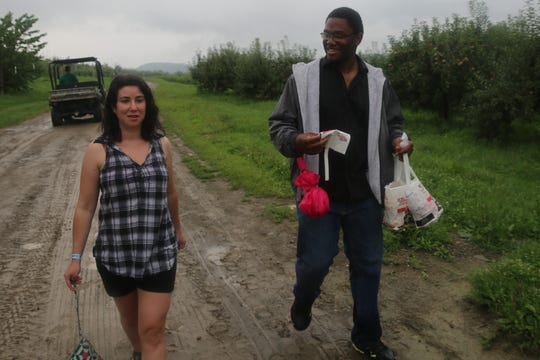 Akeem Lucky and his girlfriend, Sarah Chipkin, leave the orchard at Fishkill Farms on Saturday as the rain pours down. They picked several donut peaches as well as regular peaches.
