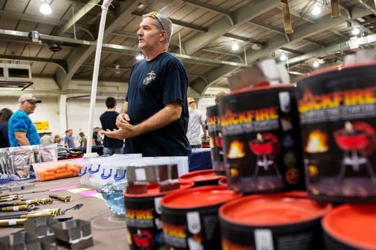 Bob Gaskin, who runs Black Dog, speaks with a show patron about the difference between the MREs that he sells compared to other companies at the Survival Expo at the York Expo Center, Saturday, August 11, 2018. The expo housed everything from essential oils to portable radiation detectors to gluten-free freeze dried meals. Gaskin also speaks at seminars about 'society ending events - the first 180 days.'