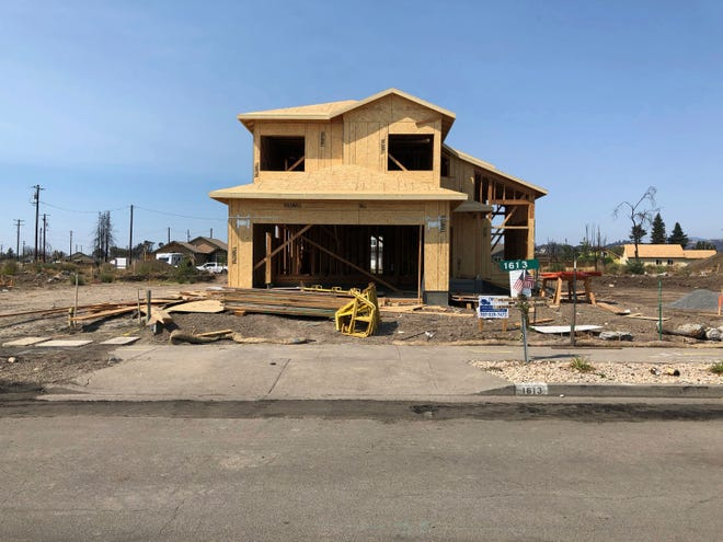 In this Friday, August 10, 2018, photo the partially rebuilt home of Debbie and Rick Serdin in the Coffey Park neighborhood in Santa Rosa, Calif. The Trump administration's tariffs have raised the cost of imported lumber, drywall, nails and other key construction materials, squeezing homeowners who seek to rebuild quickly after losing their houses to natural disasters, such as the wildfires that destroyed Coffey Park.