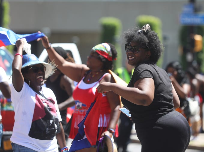 Gabby Joseph, dancing, is joined by Carmelie Diamond and Pearlie Myrthil, who are waving the flag of Haiti, as they march in the Carifest parade.  Carifest, in its 34th year, is a celebration of Caribbean culture and people.