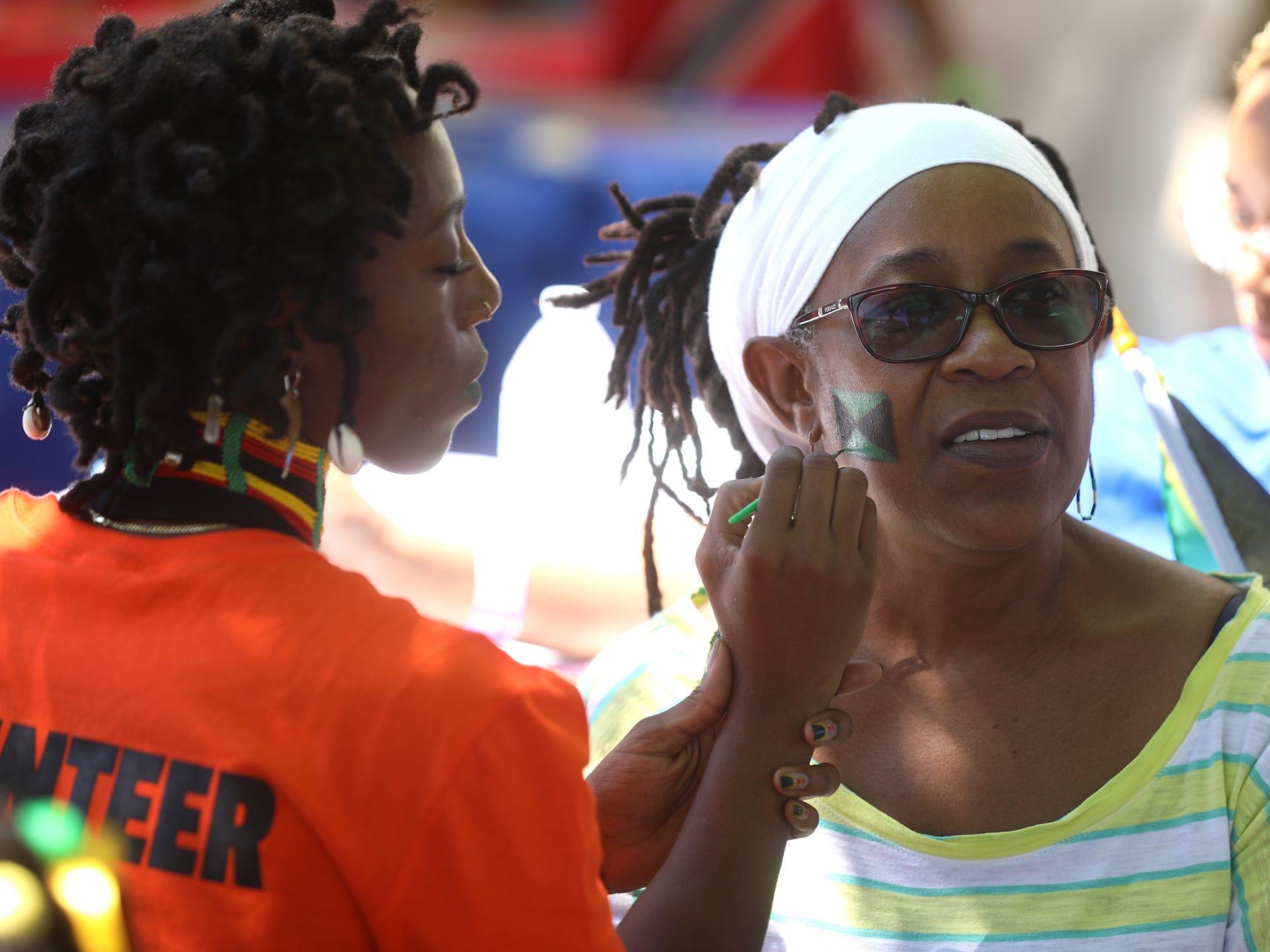 Damali Underwood paints the flag of Jamaica on Eunice Bernard's cheek.