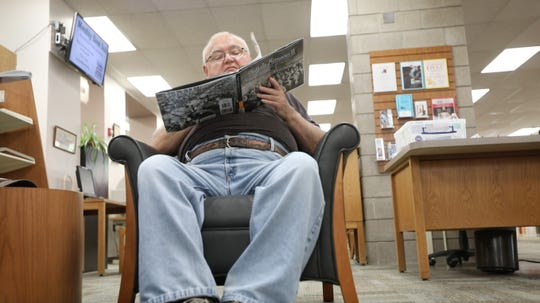 James Metzler talks politics while enjoying a book Friday at the Richmond Memorial Library in Batavia.
