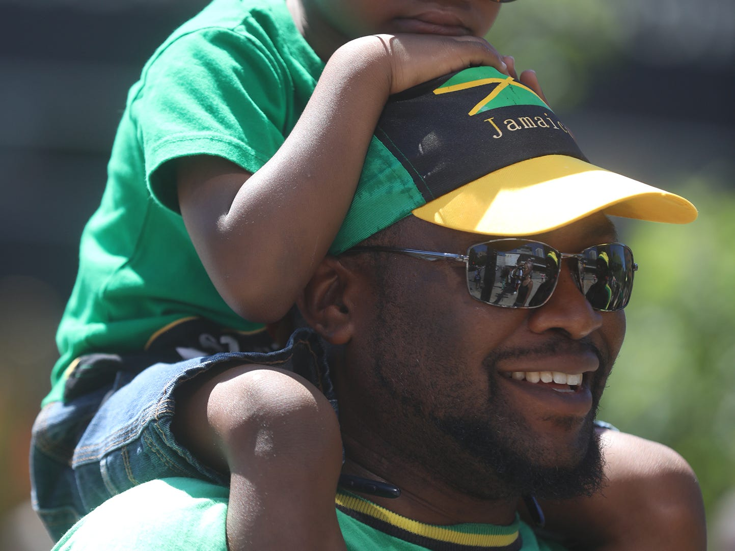 Kenzel Boxx, 5, sits on his father, Ronald's shoulders and watches Carifest parade go by them on Chestnut Street.