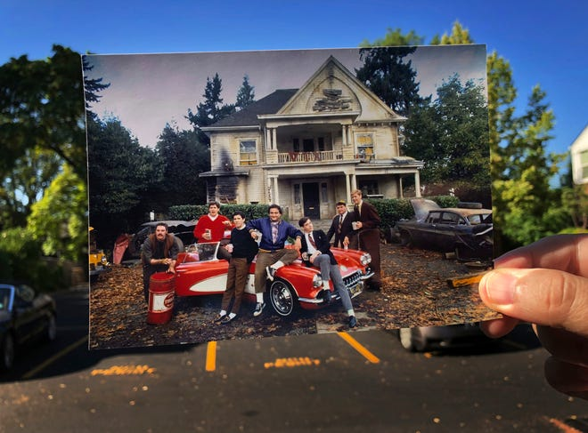 "In this July 27, 2018 photo, a photograph from the movie  Animal House is held up at the site where the fictitious Delta Tau Chi fraternity was featured in Eugene, Ore.  Forty years later, the signature location is long gone, replaced by a parking lot. The dilapidated Eugene home on East 11th Avenue that was the namesake for the movie ""National Lampoon's Animal House"" was torn down in 1986. Still, the legacy of ""Animal House"" remains, as do many of the film's locations around the Eugene area."