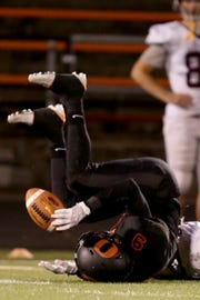 Sprague's Kobe Withers (9) rolls over after making an interception in the Forest Grove vs. Sprague football game at Sprague High School in Salem on Friday, Oct. 6, 2017.