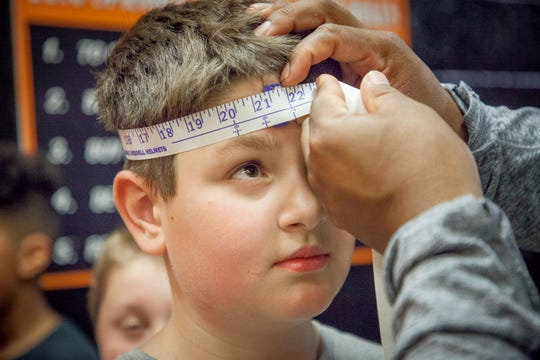 Matthew Bradley, a player for the Tualatin Valley Youth Football League, has his head measured for helmet size as participants in the youth league pick up their equipment at Sprague High School Thursday afternoon August 9, 2018 in Salem.