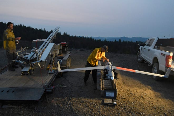 In this Tuesday, Aug. 7, 2018 photo, Ty Sibley, right, an unmanned aircraft system operator for Insitu, prepares a ScanEagle drone on a ridge south of Galesville Reservoir near Azalea, Ore. The aircraft, equipped with an infrared camera, flew for more than seven hours that night while detecting hotspots over the Taylor Creek Fire in Southwest Oregon.