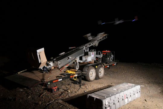 In this Tuesday, Aug. 7, 2018 photo, after the ScanEagle unmanned aircraft is loaded onto the launcher and a series of pre-flight checks are carried out, the pneumatic slingshot sends the 44-pound drone into the night sky near Azalea, Ore. The aircraft, equipped with an infrared camera, flew for more than seven hours that night while detecting hotspots over the Taylor Creek Fire in Southwest Oregon.