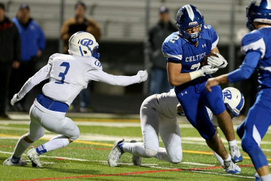 McNary's Junior Walling (2) rushes past Grants Pass' Niko Phillips (3) in the Grants Pass vs. McNary football game in the first round of the OSAA class 6A playoffs at McNary High School in Keizer on Friday, Nov. 3, 2017.