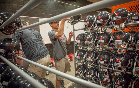 Jeremy Welborn, football coach and player safety coach for the Tualatin Valley Youth Football League grabs helmets to fit athletes as participants in the youth league pick up their equipment at Sprague High School Thursday afternoon August 9, 2018 in Salem.