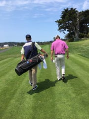 Carter Toms (right) walks up the course at Pebble Beach while his father David (left) caddies for him during the U.S. Amateur in 2018.