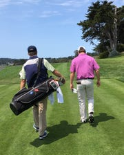 David Toms (left) totes the bag for son, Carter, during a practice round for the U.S. Amateur at Pebble Beach on Saturday.