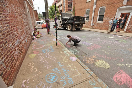 On Saturday, Aug. 11, 2018 the intersection of 4th and Water Streets in Charlottesville is filled fresh flowers and messages written in chalk where a car fatally struck a crowd one day shy of a year ago at the Unite the Right rally.