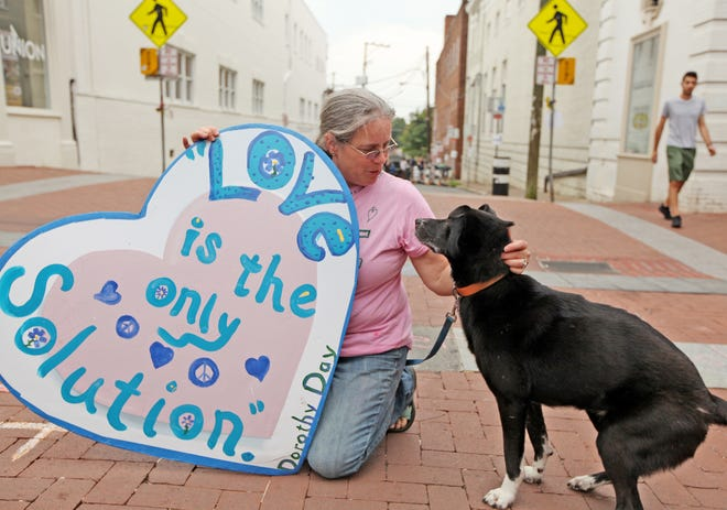 Mary Grace, of Madison, comforts her dog, Maude, as she holds her sign on the pedestrian mall at the intersection with 4th Street in Charlottesville on Saturday, Aug. 11, 2018, just a block away from where a car fatally struck a crowd one day shy of a year ago at the Unite the Right rally. Grace attended the rally last year, giving aid to those injured during the protest fights.