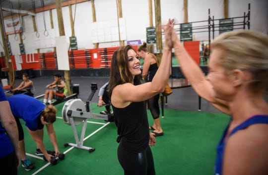 Dayna Deters shares a high-five with a class member during a training session Saturday, Aug. 11, at Integration Fitness in St. Cloud.