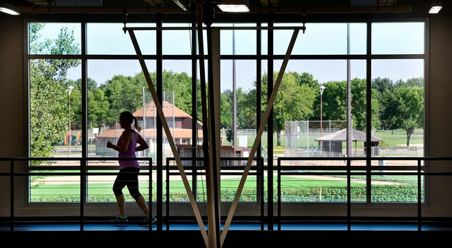 Large windows provide a colorful backdrop for people on the elevated running and walking track Friday, Aug. 10, at the St. Cloud Area Family YMCA.