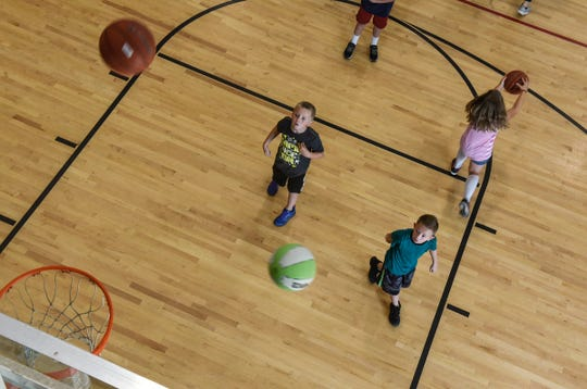 Children play basketball during a summer camp session on one of the basketball courts Friday, Aug. 10, at the St. Cloud Area Family YMCA.