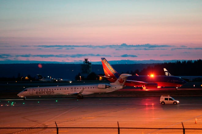 Planes sit on the tarmac at Sea-Tac International Airport after service was halted after an Alaska Airlines plane was stolen Friday, Aug. 10, 2018, in Washington.