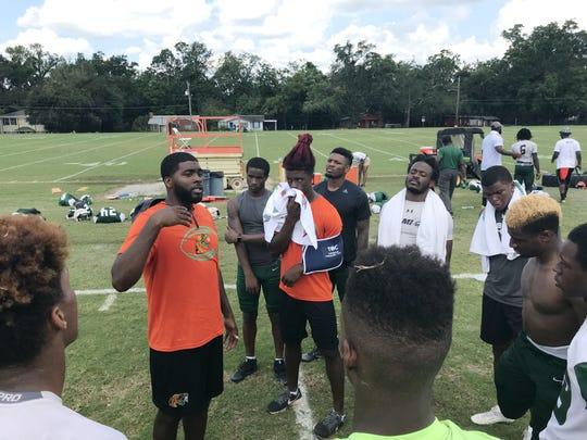 Jelani Berassa talks with his receivers after practice.