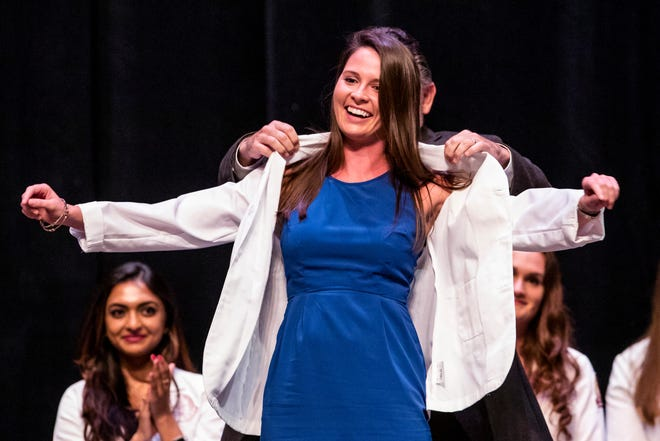 First-year student Abigail Thomas is helped into her white coat during Friday's White Coat Ceremony at FSU's Ruby Diamond Concert Hall.