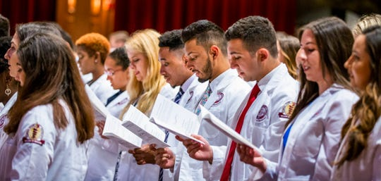 Participants in Friday's White Coat Ceremony stand and recite the Student Oath in front of their families and friends.