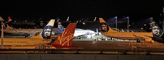 Alaska Airlines and other planes sit on the tarmac at Sea-Tac International Airport Friday evening, Aug. 10, 2018, in SeaTac, Wash. An airline mechanic stole an Alaska Airlines plane without any passengers and took off from Sea-Tac International Airport in Washington state on Friday night before crashing near Ketron Island, officials said. (AP Photo/Elaine Thompson)